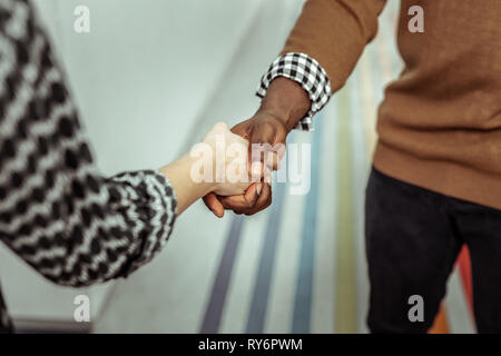 Di carnagione scura uomo forte stringono le mani con piccola donna pallida Foto Stock