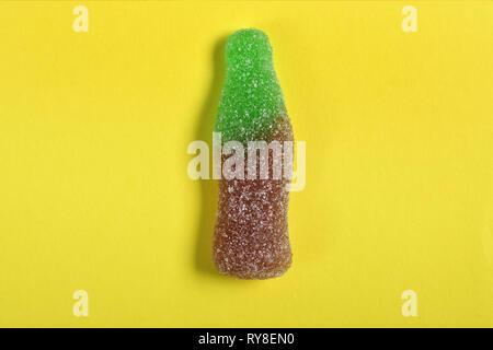 Bottiglia coke candy su sfondo giallo Foto Stock