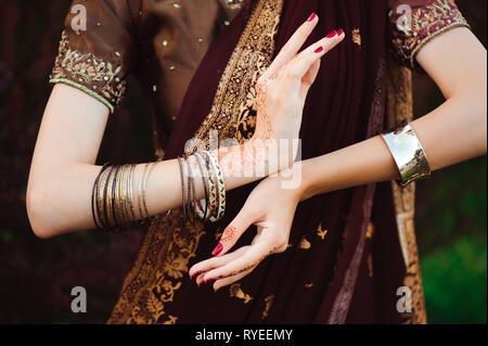 La donna le mani con il nero mehndi tattoo. Le mani della sposa indiano ragazza con black henna tattoos. Moda. Foto Stock