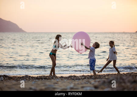 Tre bambini che giocano con un enorme palloncino rosa sulla spiaggia al tramonto Foto Stock