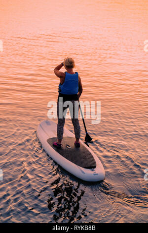 La donna in piedi sul pedalò sul Lago di Galve in Trakai in Lituania. Al tramonto Foto Stock