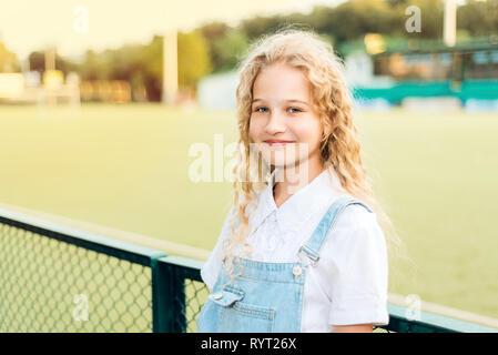 Ritratto di una giovane e bella bionda studentessa con capelli ricci in un blu denim globale. Foto Stock