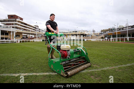 Un groundsman taglia erba prima di Gold Cup giorno del 2019 Cheltenham Festival a Cheltenham Racecourse. Foto Stock