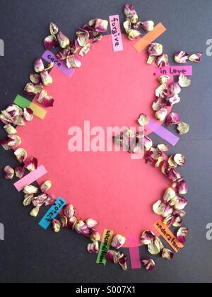 Cuore di carta con petali di rosa e gli adesivi con parole scritte Foto Stock