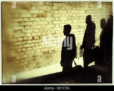 Ombre di tre persone su un muro di mattoni,Shoreditch,London , REGNO UNITO Foto Stock