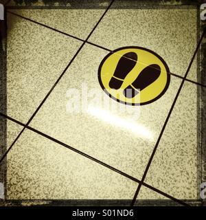 Aspettare qui segno sul pavimento piastrellato Foto Stock
