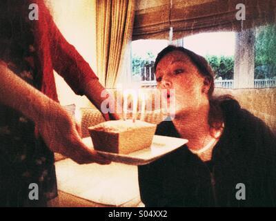 Donna soffiando fuori candele su una piccola torta di compleanno Foto Stock