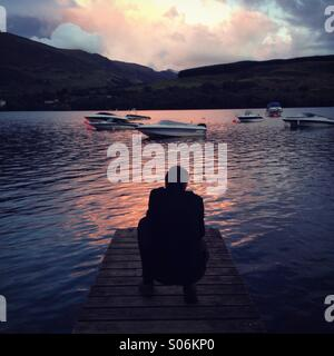 Un uomo accovacciato che si affacciava su un scozzese loch al tramonto Foto Stock