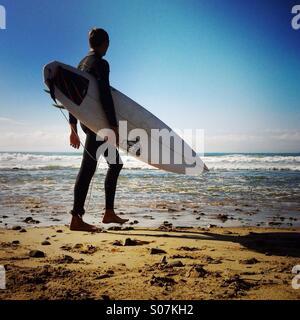 Un surfista passeggiate fino alla spiaggia. Ventura California USA.