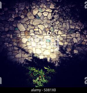 Muro di pietra con alluvione luce di notte Foto Stock