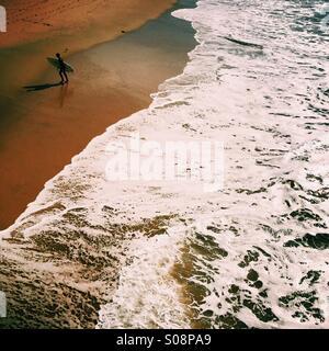 Un surfista maschio passeggiate fino alla spiaggia. Manhattan Beach, California USA.