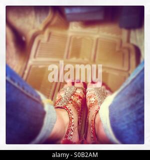Guardando verso il basso sulla blue jeans e dipinte di rosso le dita dei piedi in perline etniche sandali sulla parte superiore di plastica beige Matt in un'auto.