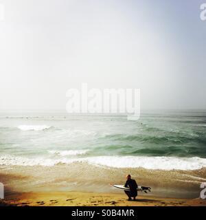 Un surfista attende sulla spiaggia. Manhattan Beach, California USA. Foto Stock