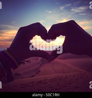 Silhouette di mani in forma di cuore al tramonto Foto Stock