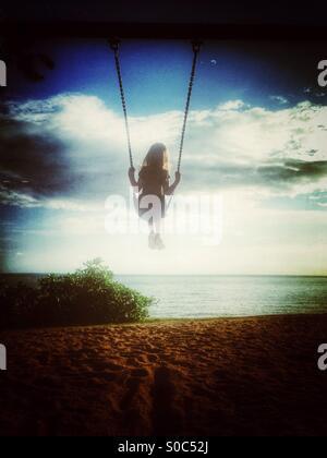 Giovane ragazza su altalena in spiaggia. Foto Stock