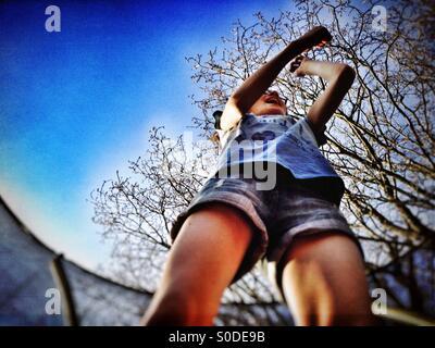 Ragazza giovane rimbalzare sul trampolino Foto Stock