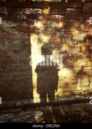 Ombra di un ragazzino su un muro di mattoni Foto Stock
