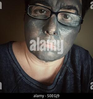 Una donna che indossa occhiali con una maschera di fango sul suo viso Foto Stock