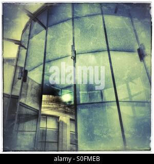 Vecchio edificio si riflette in un edificio moderno in vetro anteriore. Foto Stock