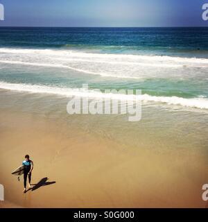 Un surfista maschio passeggiate fino alla spiaggia. Manhattan Beach, California. Stati Uniti d'America.