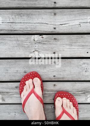 Red flip flop su una banchina in legno in estate cottage, Finlandia Foto Stock