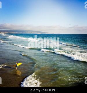 Un surfista passeggiate fuori per il surf. Manhattan Beach, California USA. Foto Stock