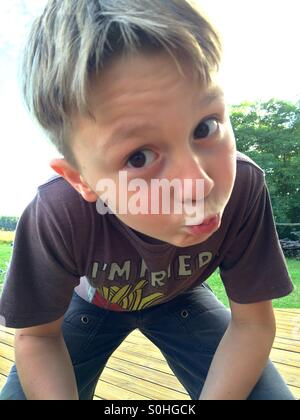 10 anno vecchio ragazzo di piegarsi per un bacio Foto Stock