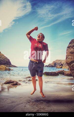Un ragazzo su una spiaggia di sabbia a salti di gioia. Un Cornish beach con l'oceano dietro di lui. Foto Stock