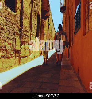 Madre e figlio camminando mano nella mano lungo un vicolo in Mdina Malta Foto Stock