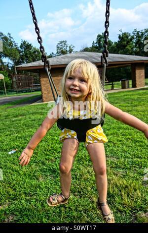 Ragazza giovane giocando su swing in posizione di parcheggio Foto Stock
