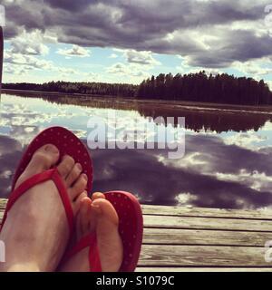 Una donna con red flip flop brividi su un molo in legno Foto Stock