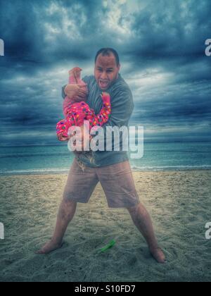 Il padre e la bambina giocando sulla spiaggia Foto Stock