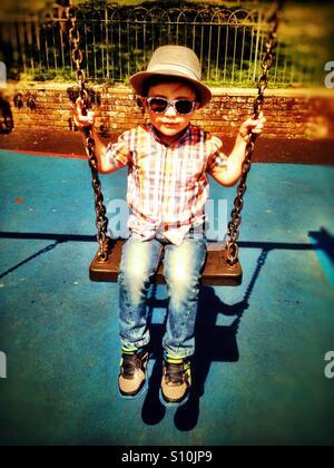 Un giovane ragazzo che indossa un cappello e occhiali da sole gioca su s'altalena nel parco. Foto Stock