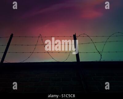 Barb wired parete contro un cielo notturno Foto Stock