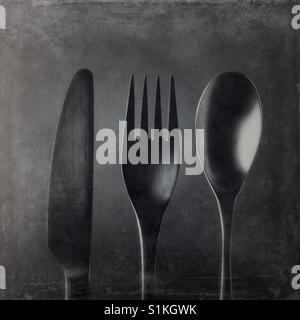 Un bianco e nero close up shot di overhead di un coltello e una forchetta e un cucchiaio