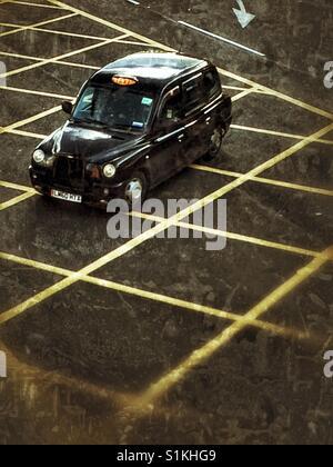 Guardando verso il basso a partire da sopra su un Black Cab di Londra o taxi accelerando su pericolo giallo linee su una strada di Londra. Foto Stock
