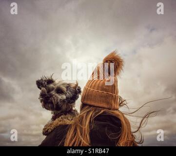 Una moda giovane ragazza in una maglia di lana hat tenendo il suo cane scruffy sulle sue spalle con un cielo tempestoso Foto Stock
