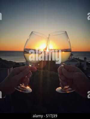Due bicchieri tintinnanti al tramonto. saluti!