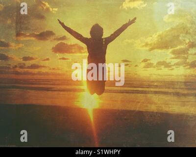 Ragazzo salta con le braccia aperte in spiaggia al tramonto Foto Stock