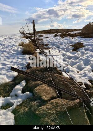 La rottura di un filo spinato su una coperta di neve altopiano della Montagne Drakensberg segna il confine tra il Sudafrica e il Lesotho. Foto Stock