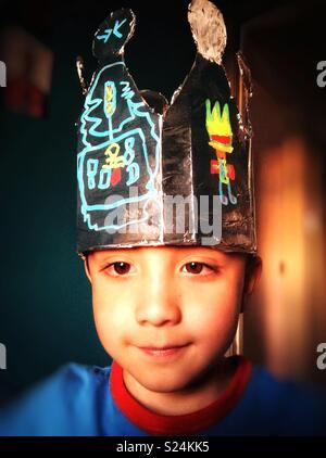 Ritratto di un giovane ragazzo che indossa una corona fatta in casa. Foto Stock