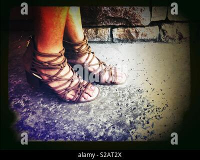 Donna che indossa marrone leggero strappy sandali gladiator fuori nel patio in una calda giornata estiva Foto Stock