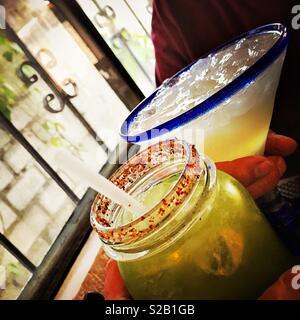 Un cetriolo margarita con una speziata salati rim è mostrato con un tradizionale margarita durante l'happy hour. Foto Stock
