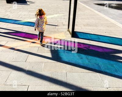 Giovane ragazza Toddler camminando sul marciapiede colorato all'aperto Foto Stock