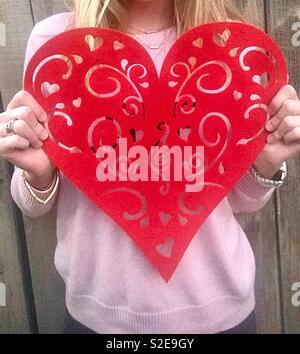 Io vi amo. Una ragazza adolescente che indossa un maglione rosa tenendo un cuore rosso per il giorno di San Valentino. Stati Uniti d'America, America Foto Stock