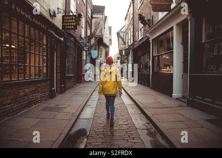 Una vista posteriore di una moda giovane ragazza camminare lungo una storica strada medievale noto come il caos nella storica città di York Regno Unito Foto Stock