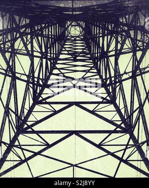 Guardando in alto, da sotto un traliccio di elettricità Foto Stock