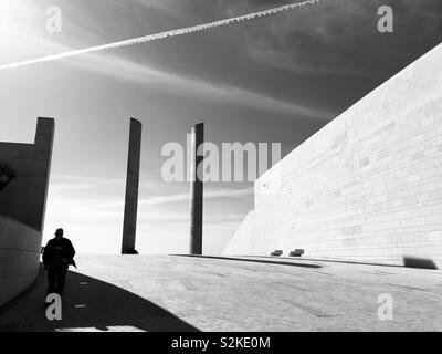 Architectural Design contemporaneo dettagli dal centro Champalimaud per l'ignoto. Lisbona, Portogallo, dell'Europa. Un maschio adulto figura in ombra cammina verso la telecamera. Foto Stock