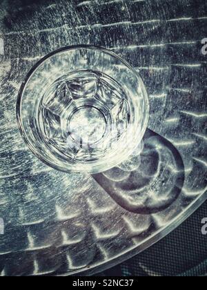 Acqua in vetro chiaro sul tavolo in metallo, all'aperto con disco ombre dalla luce solare.