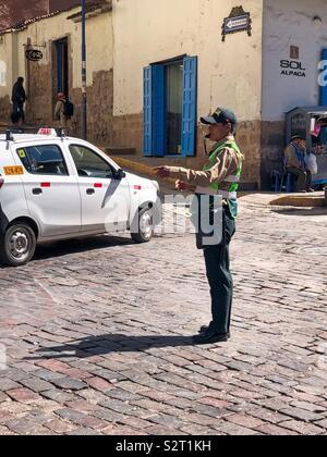 Il traffico peruviano cop polizia poliziotto che dirige il traffico su una strada a ciottoli nel Cusco Cuzco Perú Perù. Foto Stock
